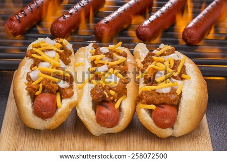 Chili Hot Dogs with Cheese and Onions on a Wood Cutting Board with Hot Dogs on a Hot Flaming Barbecue Grill Background - stock photo