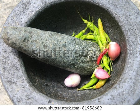 Chili pepper and shallots in stone mortar, Thai food cooking - stock photo