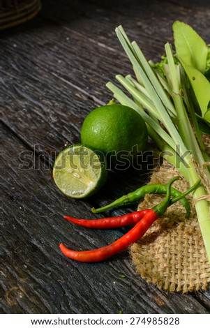 chili pepper with lime and Kaffir lime leaf on old wooden table, Thai style cooking ingredient - stock photo