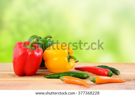 Chili peppers and bell peppers on wooden. - stock photo