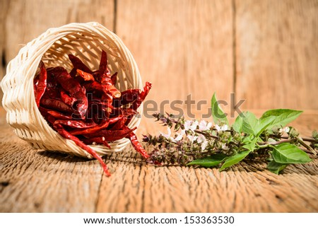 chili peppers and fresh herb on wood background