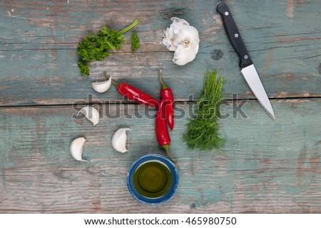 Chili peppers, garlic, herbs and oil on a wooden table, stock picture