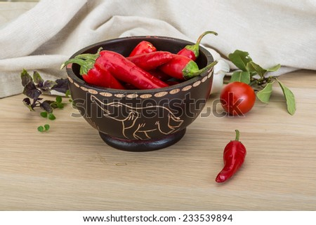 Chili peppers in the bowl on wooden background
