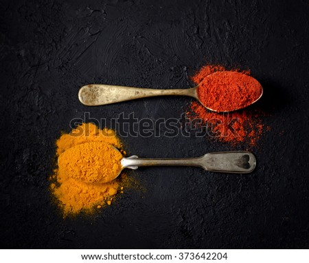chili powder and turmeric in a vintage spoon on a dark background - stock photo