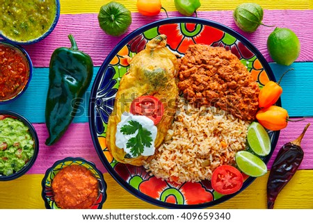 Chili relleno chili pepper poblano filled with cheese in dish with with rice and frijoles beans - stock photo