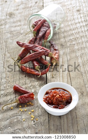 Chili sauce with dried chillies falling out of jar on rustic wood