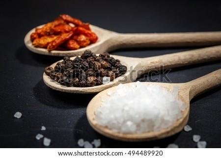 Chili with black pepper and salt on rustic stone background. Overhead view food photography.