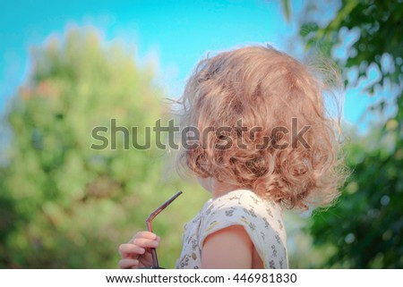 Chill out in the daytime. A toddler girl with blonde curly hair is drinking milk from a straw turing away in the public park. - stock photo