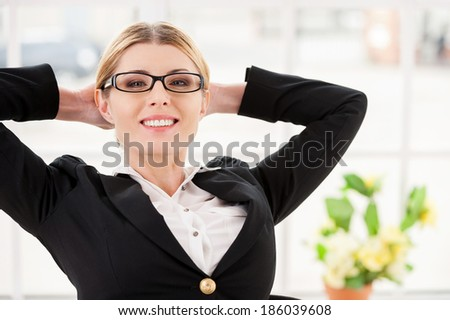 Chill time. Happy mature woman in formalwear holding hands behind head and smiling while sitting at her working place - stock photo