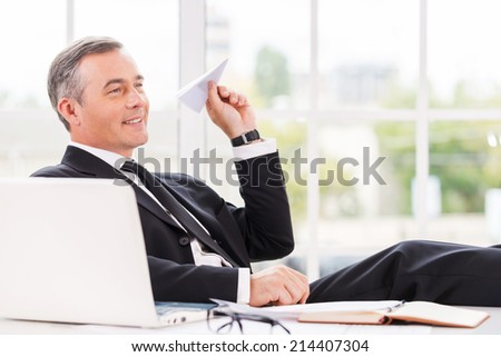 Chill time. Playful mature man in formalwear holding paper airplane and smiling while sitting at his working place - stock photo