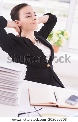 Chill time. Side view of cheerful young business woman holding head in hands and keeping eyes closed while sitting at her working place - stock photo
