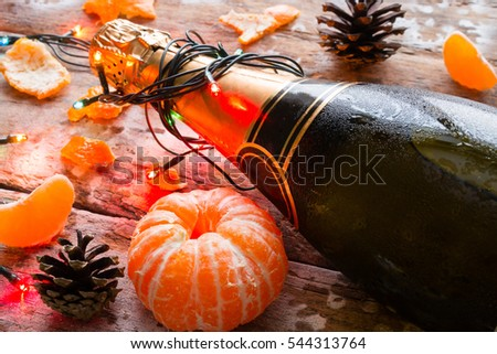 chilled bottle of champagne with garland closeup and tangerines on a wooden background
