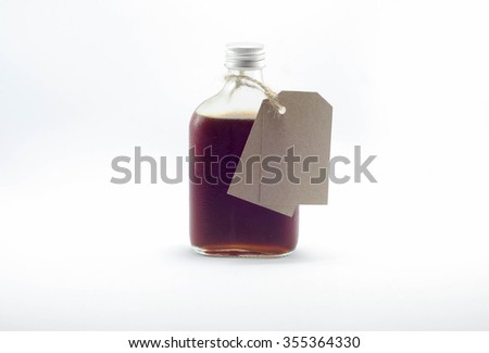 Chilled bottle of cold-brewed coffee with tag on white background - stock photo