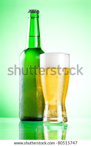 Chilled green bottle with condensate and a glass of beer lager on a green background