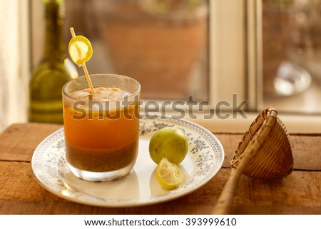Chilled jaljeera served in a glass, kept on a wooden table. - stock photo