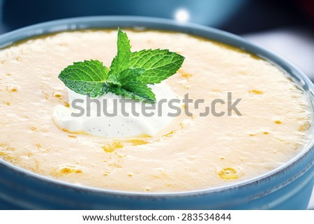 Chilled peach soup with fresh vanilla flavored sour cream. Extreme shallow depth of field with selective on bowl in foreground.  - stock photo