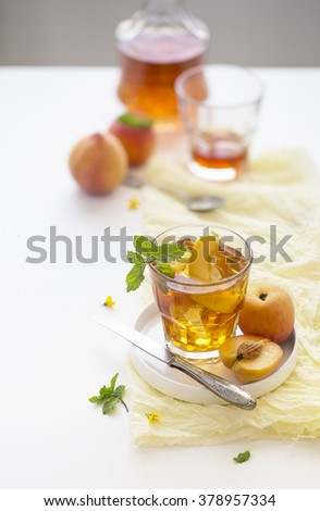 Chilled peach tea in glass with fresh cut peaches on white background. - stock photo
