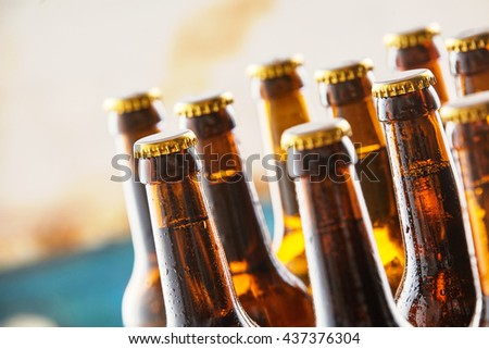Chilled refreshing beers standing on a counter in a bar or pub with closeup focus to the necks and unopened tops and copy space conceptual of celebrating the Oktoberfest