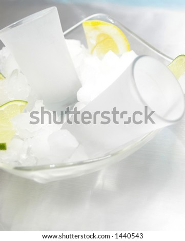 Chilled shot glasses on ice with citrus.