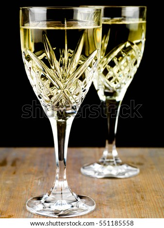 Chilled White Wine in a Cut Crystal Glass Against a Black Background