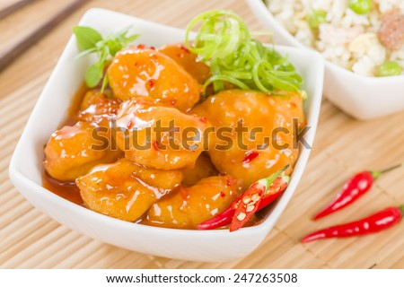 Chilli Chicken - Asian style battered and deep fried chicken in chilli sauce served with special fried rice. - stock photo