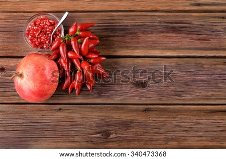 Chilli cluster with pomegranate seeds and pomegranate in the bowl of an old wooden board - stock photo