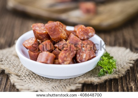 Chilli flavoured Sausages (German Mettwurst) on wooden background (selective focus) - stock photo
