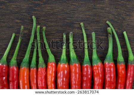 Chillies in a row on wood table  - stock photo