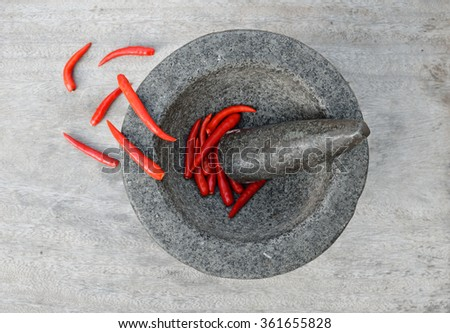 Chillies in Mortar with Pestle on a wooden table for spicy thai ingredient - stock photo