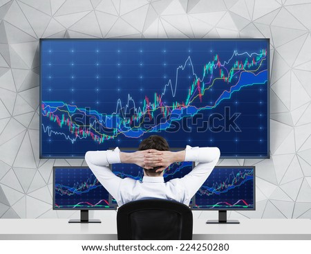 Chilling Trader in front of forex screens  - stock photo