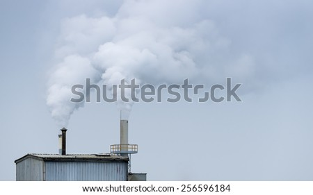 Chimney in an industrial area. - stock photo