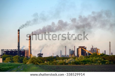 Chimney of a Power plant against blue sky - stock photo
