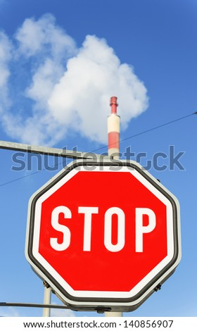 chimney of an industrial company and stop sign. symbolic photo for environmental protection and ozone.