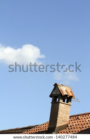 chimney on a roof made of red terracotta tiles - stock photo