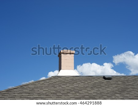Chimney, pink chimney against a blue sky with clouds