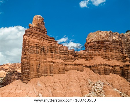Chimney Rock, a red cliff of sandstone is backed by a deep blue sky in the Utah desert of Capitol Reef National Park. - stock photo