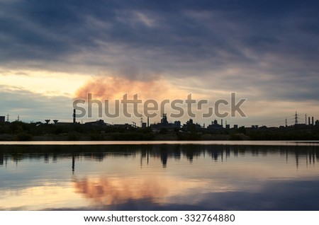 Chimney smoldering mirroring in water with rain clouds - stock photo