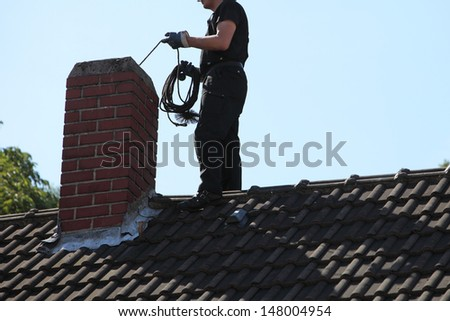 Chimney sweep cleaning a chimney standing balanced on the apex of a house roof lowering equipment down the flue - stock photo