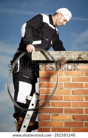 Chimney sweep man in work uniform cleaning brick style chimney - stock photo