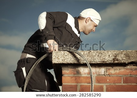 Chimney sweep man in work uniform cleaning chimney on building roof - stock photo