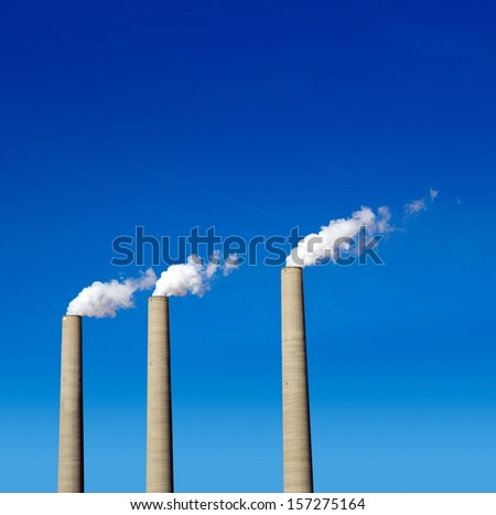 Chimney white smoke three in a row on a blue sky - stock photo