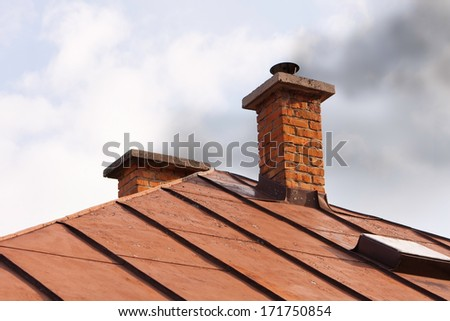 Chimney with neglected maintenance emitting air pollution due to improper burn of solid fuels in wood stove during heating season.  - stock photo