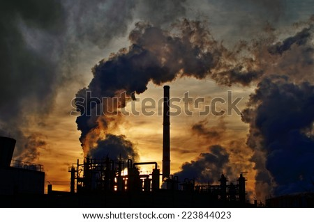 Chimneys and dark smoke over chemical factory at sunset