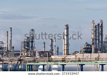 chimneys of oil refinery in winter against a cloudy sky