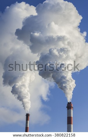 Chimneys with dramatic clouds of smoke, example of the impact of pollution on the environment. - stock photo