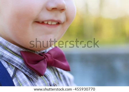 Chin and smiling mouth of little cute boy on bow tie outdoor - stock photo