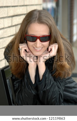 Chin in hands, this female teen smiles as she enjoys the sunshine.  Red rimmed sunglasses.  Black coat. - stock photo