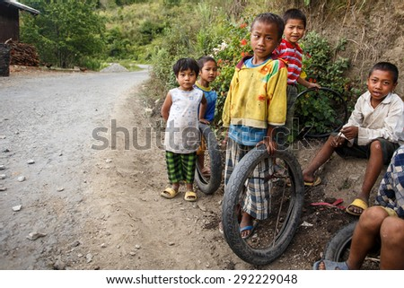 CHIN STATE, MYANMAR - JUNE 16 2015: Children play in the street of a village in the recently opened to foreigners area of Chin State - western Myanmar (Burma) - stock photo