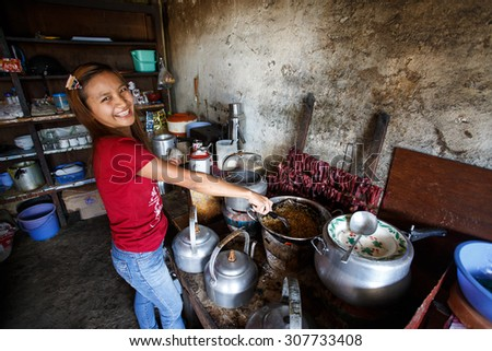 CHIN STATE, MYANMAR - JUNE 18 2015: Cute girl cooks traditional food in the recently opened for tourists Chin State Mountainous Region, Myanmar (Burma) - stock photo
