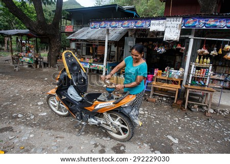 CHIN STATE, MYANMAR - JUNE 16 2015: Lady refills gasoline from a bottle in the recently opened to foreigners area of Chin State - western Myanmar (Burma) - stock photo